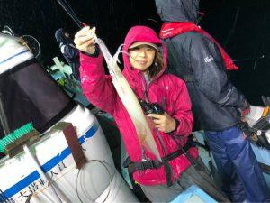 船の上で魚を持つ女性