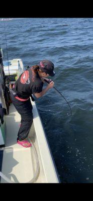 船の上でブリを釣る女性