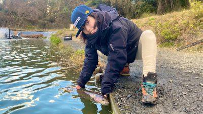 釣り場で50cm級のレインボーを持つ女性