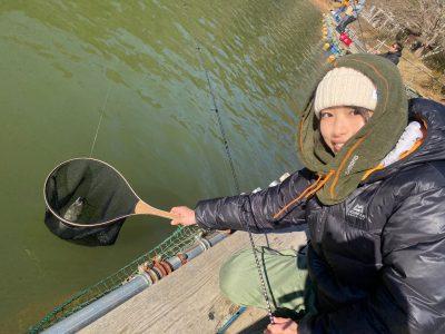 管釣りで釣れた魚を持つ女性