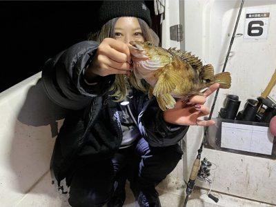 魚を前に突き出して撮影する女性